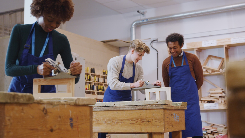 Male tutor with carpentry student in workshop studying for apprenticeship at college using wood plane - shot in slow motion | Shutterstock HD Video #1049966959