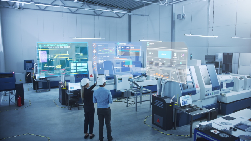 Industry 4.0 Factory: Two Engineers Uses Digital Tablet Computer with Augmented Reality Software to Connect with CNC Machinery, Robot Arm and Visualize Maintenance and Diagnostics of the Equipment Royalty-Free Stock Footage #1049967940