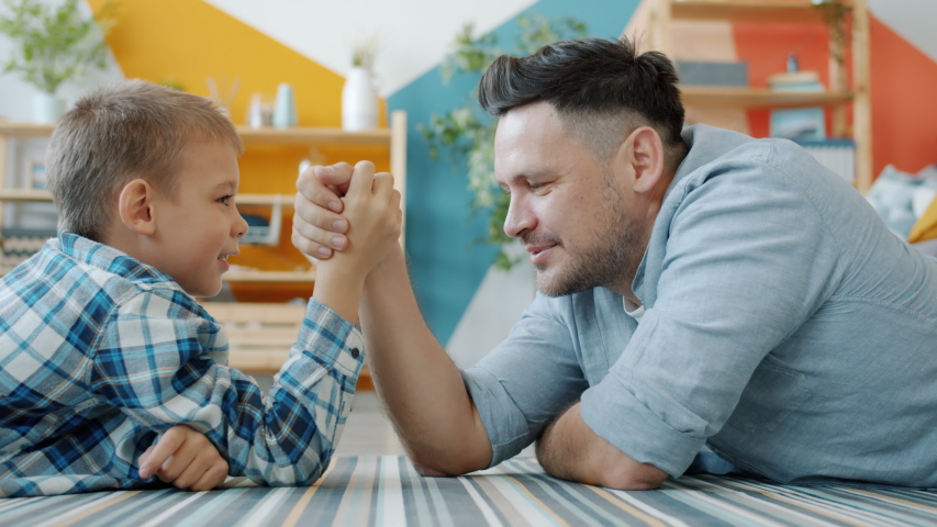Middle-aged man and little boy are practising arm wresting at home enjoying activity, child is winning. Modern pastime, family relationship and fun concept.