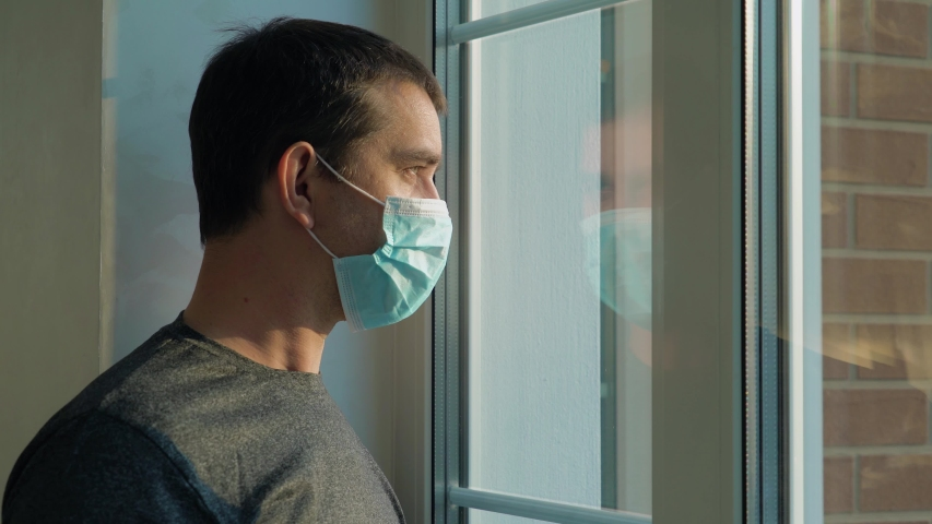 Coronavirus outbreak situation. Infected man on self-isolation looks at the street through the window of house. Man in a medical mask near the window. Man in surgical mask looking out his home window. | Shutterstock HD Video #1049972392