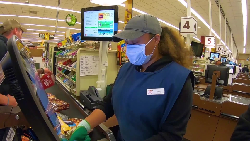 CIRCA 2020 - grocery store supermarket checkout workers are essential during the coronavirus Covid-19 epidemic outbreak.