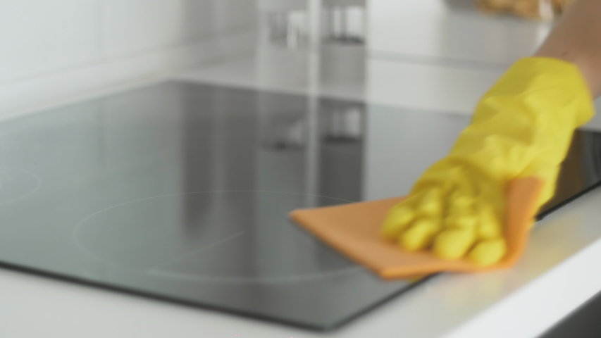 Cleaning cooktop cooking panel in kitchen with fat remover spray and orange rag by a woman in yellow rubber gloves.