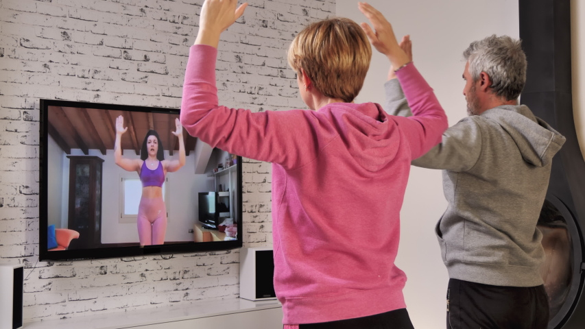 Couple follow workout fitness lesson online at home,do exercise watching their personal trainer livestreaming on tv social media web channel | Shutterstock HD Video #1049977993