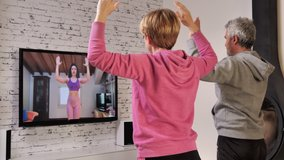 couple follow workout fitness lesson online at home,do exercise watching their personal trainer livestreaming on tv social media web channel