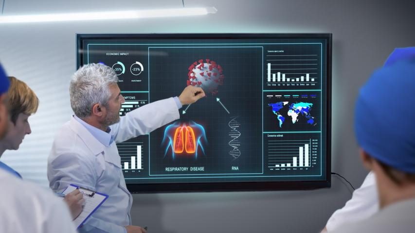 Medical team of doctors discussing coronavirus covid-19 data on digital display screen showing the virus outbreak and the infection on human body  Royalty-Free Stock Footage #1049977996