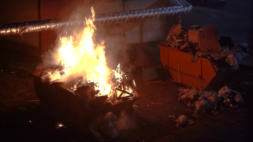 Trash cans burn in the city at night