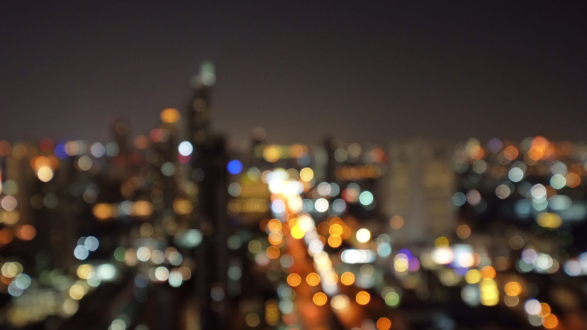 Bokeh background of skyscraper buildings in Bangkok city, Thailand with lights, Blurry photo at night time. Cityscape Royalty-Free Stock Footage #1049988337