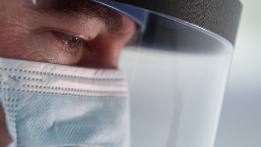 Male Lab technician working in lab with face mask and shield viewing side of face. Royalty-Free Stock Footage #1049989696