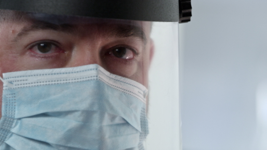 Male lab technician wearing face mask and shield in medical lab. | Shutterstock HD Video #1049989708