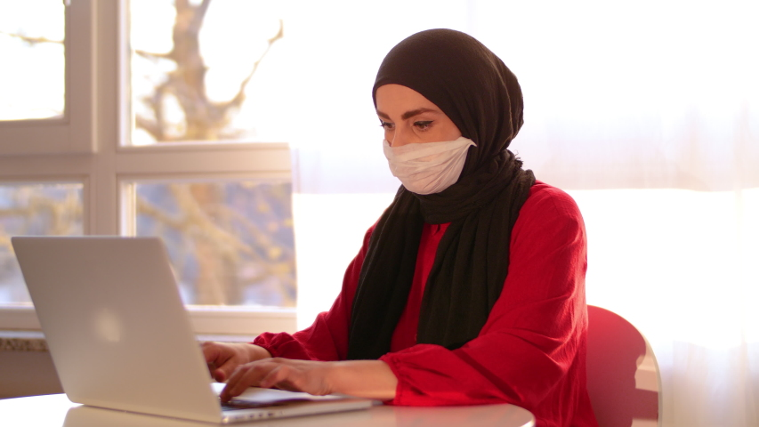 Sick young arab hidjab businesswoman with wears face mask using computer coughing at home office. Ill female worker working distantly self-isolating having coronavirus flu infection symptom concept.  Royalty-Free Stock Footage #1049991862