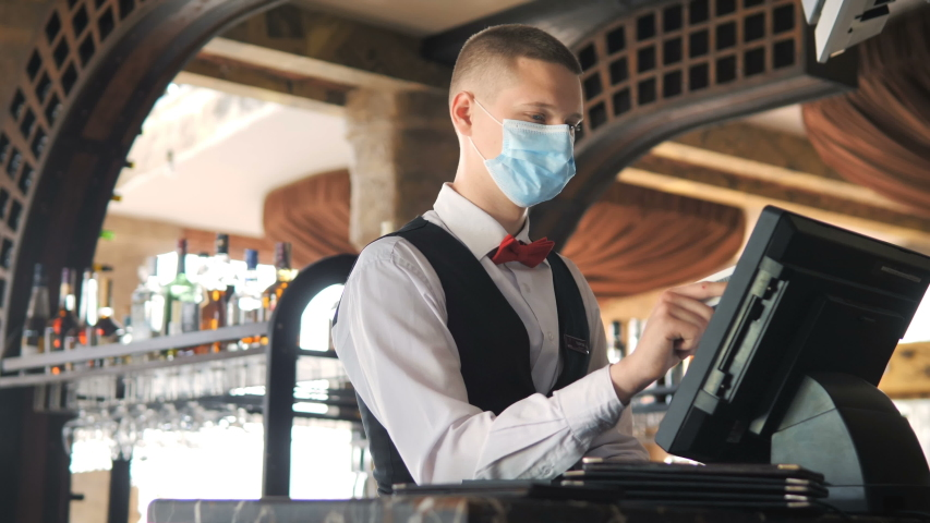 Man or waiter in medical mask at counter with cashbox working at bar or restaurant