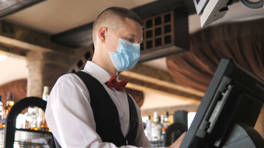 Man or waiter in medical mask at counter with cashbox working at bar or restaurant | Shutterstock HD Video #1050001858