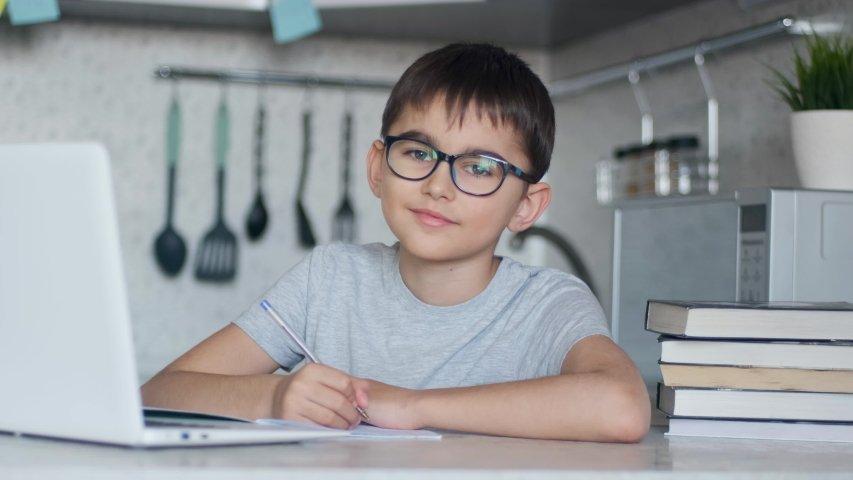 The child in glasses teaches lessons while at home sitting in the kitchen at the table using a laptop, books, notebook and looking at the camera. Left camera movement | Shutterstock HD Video #1050007384