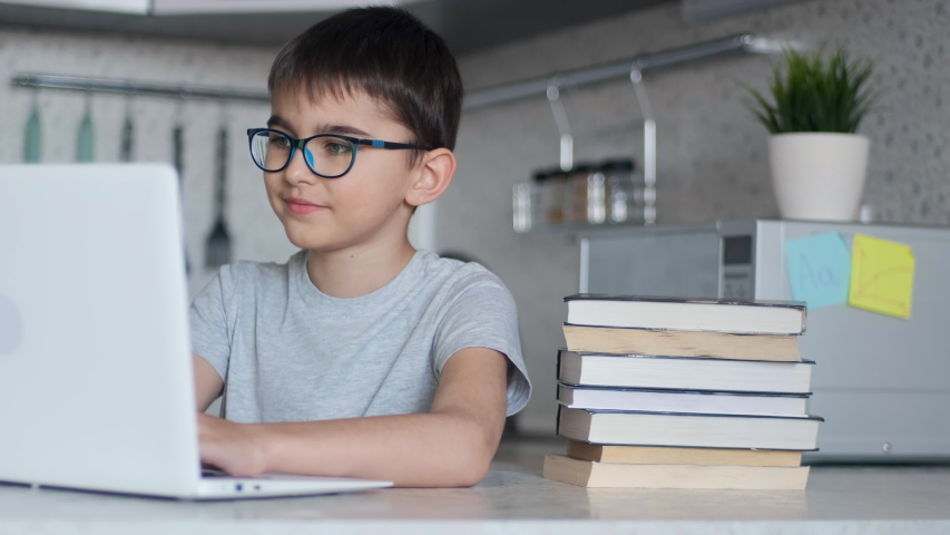 Online learning, distance lesson, education at home, technology for kids. Boy with textbooks doing school homework and using digital tablet computer at home | Shutterstock HD Video #1050007465
