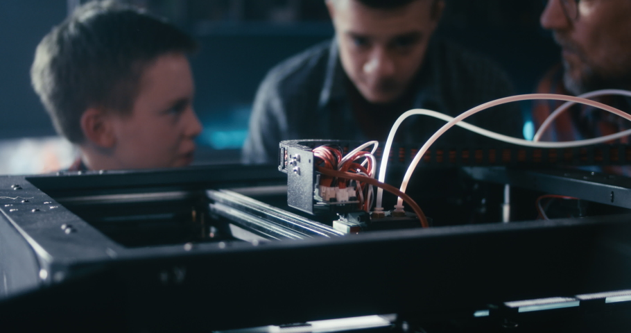 Medium shot of a teacher and his students using a 3D printer