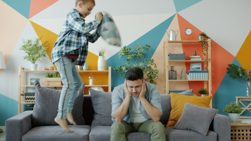 Stressed dad suffering from headache while naughty child beating him with pillow jumping on sofa having fun in apartment. Childhood and parenting concept. | Shutterstock HD Video #1050030994
