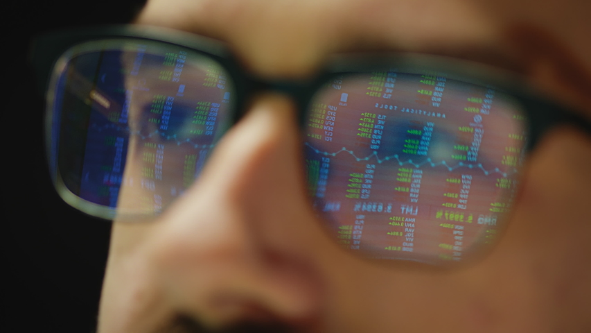 Close up reflection of stock market graphs in broker glasses. Royalty-Free Stock Footage #1050032845