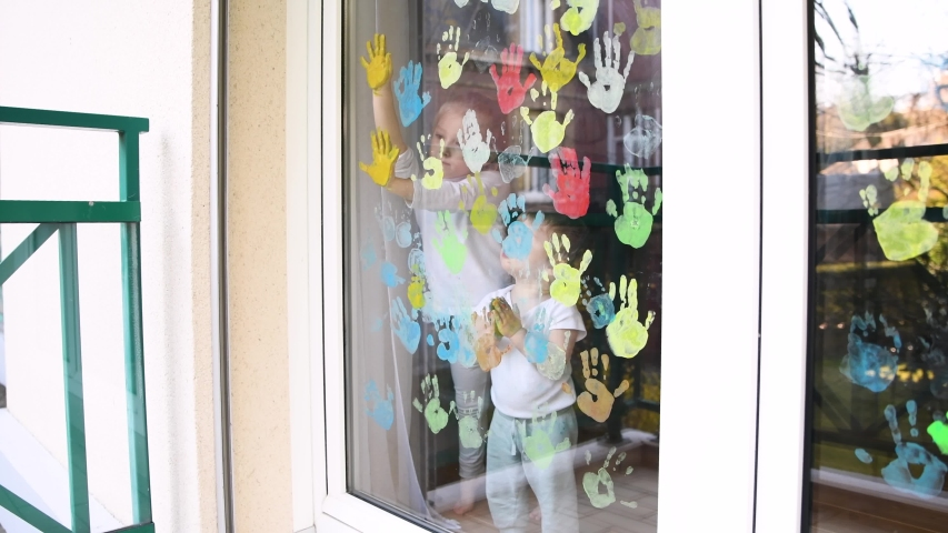 The kids paint with palms on the window. Quarantine | Shutterstock HD Video #1050037306