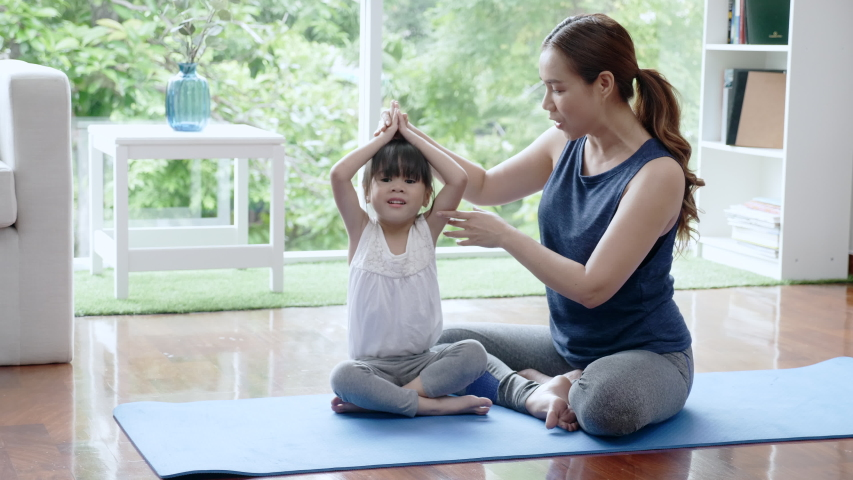 Asian family Mother is teaching her daughter to do yoga at home. Practice your physical workout skills to be strong and to concentrate. Holiday activities that make many families happy Royalty-Free Stock Footage #1050043819
