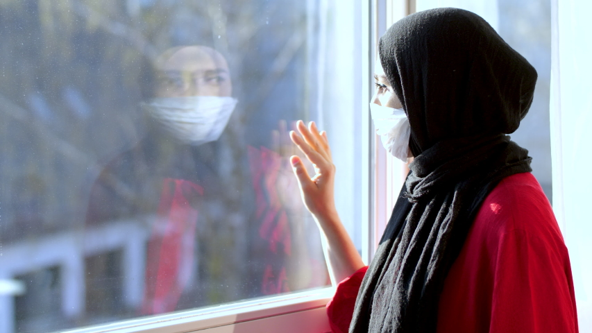 COVID-19 Pandemic Coronavirus Woman with hijab with wearing face mask looks out the window isolation. arab woman hijab. Muslim woman with hijab arab.