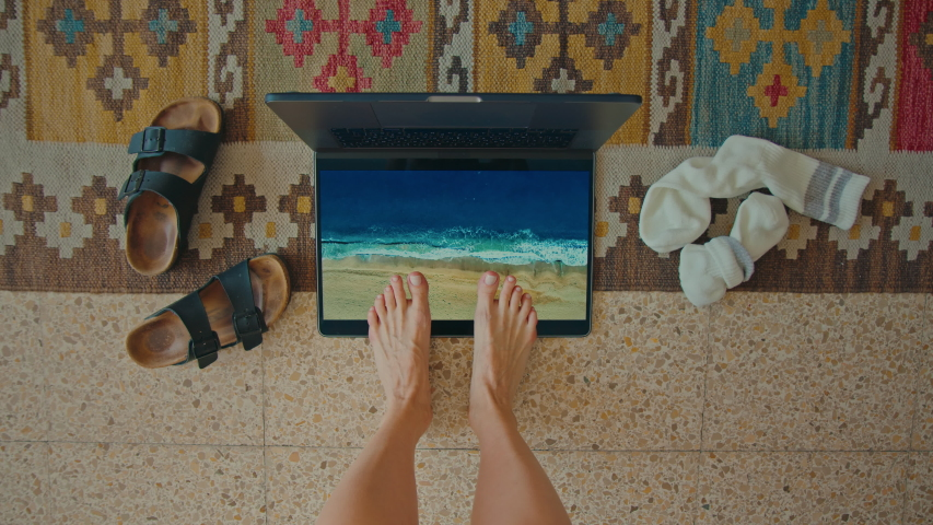 Top view on woman bored at home during coronavirus quarantine lockdown. Sad and bored look forward to vacation, put feet in imaginary beach sand on laptop. Concept cancelled summer holiday Royalty-Free Stock Footage #1050049534