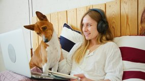 Happy young female pet owner look at laptop with basenji dog. Cute adorable puppy look at comedy funny movie. Girl and her dog have fun, talk to family and friends on video chat conference app