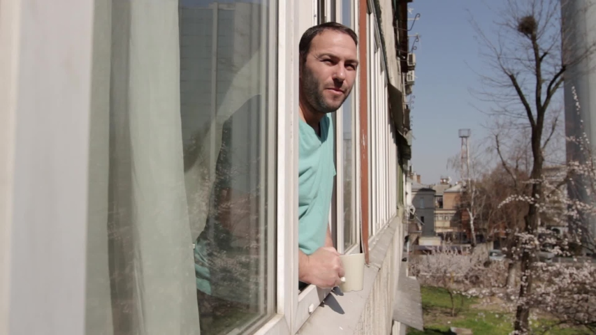 A man stands near an open window with a cup in his hand, smiles and waves hello, spreads his arms to the sides. camera movement through the window frame, from apartment to street from left to right. | Shutterstock HD Video #1050058591