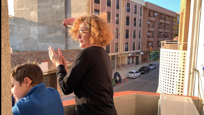 Spanish woman and her son applaud from the balcony for COVID 19.