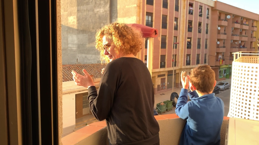 A Spanish woman and her son applaud from the balcony of their apartment for the COVID 19 pandemic health team. | Shutterstock HD Video #1050081400
