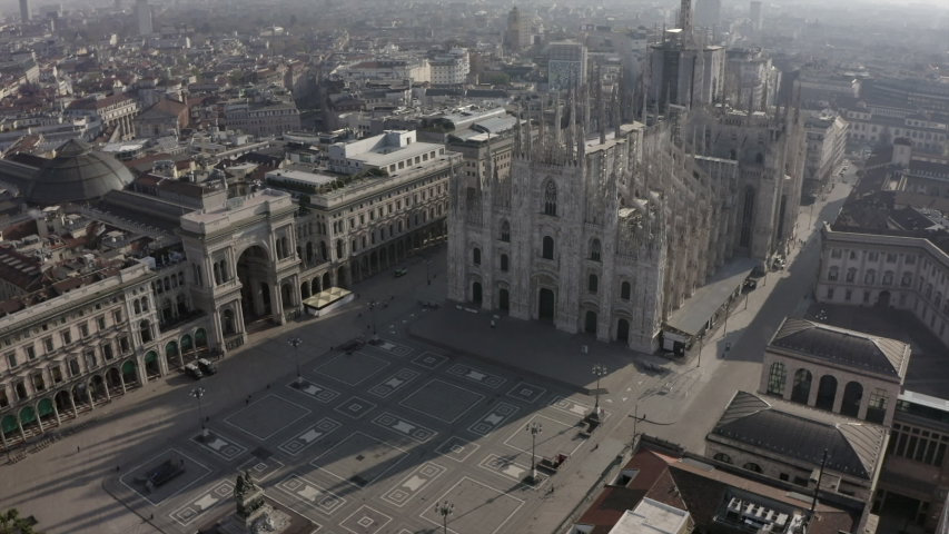 Daily life in Milan, Italy during COVID-19 pandemic. Milano, Italian city and coronavirus outbreak. Aerial view of Piazza Duomo. Historic monument and religious building seen from drone flying in sky
