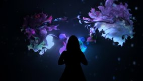 Girl plays with interactive video installation, New art form, generative graphics. Silhouette of girl draws multi-colored paints interactive installation. Woman does concept art with augmented reality