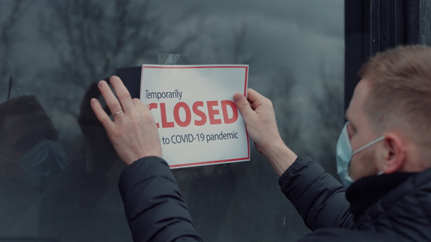 Caucasian male wearing medical mask puts a Temporary closed due COVID-19 pandemic sign on a window. Coronavirus pandemic, small business shutdown | Shutterstock HD Video #1050091936