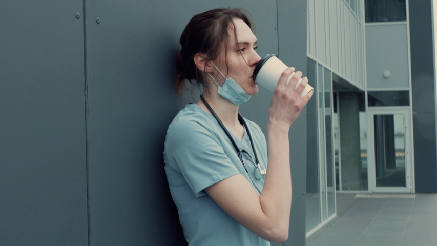 Portrait of tired exhausted nurse or doctor having a coffee break outside in the morning. COVID-19, Coronavirus pandemic. ARRI Alexa Mini