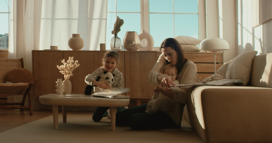 Mother working from home, having a phone call, while her daughters distract her and drawing attention. Shot on RED Dragon | Shutterstock HD Video #1050092011