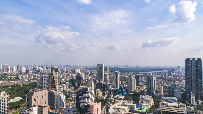 Bangkok business district city center and Chao Phraya River, with cloud pass over buildings and skyscrapers; zoom out – Time Lapse | Shutterstock HD Video #1050099325