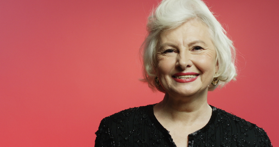 Portrait of old gray-haired beautiful woman in fancy black blouse smiling joyfully to camera on pink wall background. Close up of Caucasian senior lady with smile. Happy retired lady.
