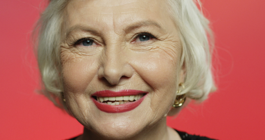 Close up of beautiful gray-haired Caucasian old woman with wrinkles and red lips smiling cheerfully to camera on pink background. Portrait of pretty happy grandmother. Senior female face with smile.