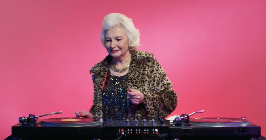 Retro stylish Caucasian female pensioner in fancy outfit of 70s 80s playing music at DJ equipment over pink wall at party. Vintage concept of old woman working as dj disco.