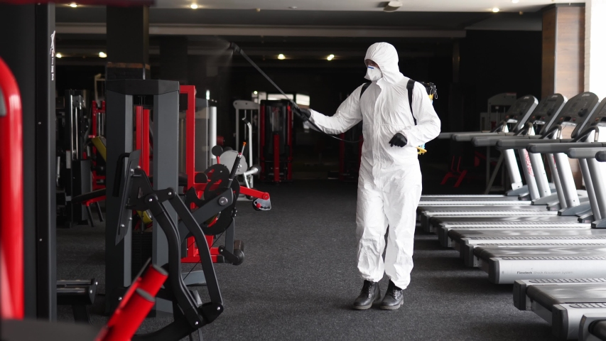 Hazmat worker disinfects gym fitness equipment from coronavirus covid-19 hazard with antibacterial sanitizer sprayer on quarantine. Man in protective suit cleans training apparatus at workout area. Royalty-Free Stock Footage #1050115951