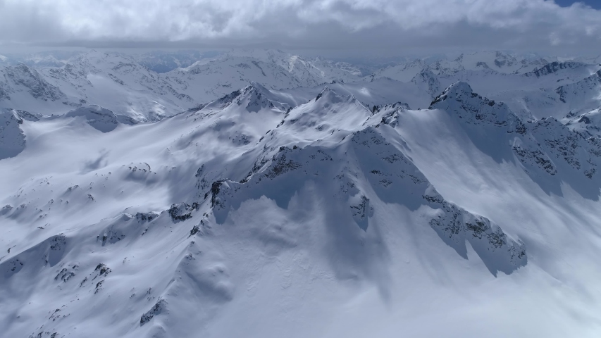 From great heigh fairytale mountain landscape snow covered alpine sharp peaks. Wild winter untouched inaccessible nature Russia Switzerland Alps abstract. Thick white clouds. Open space. Aerial 4K