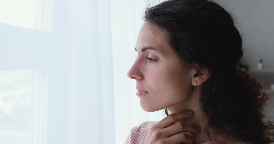 Pensive worried young adult woman looking outside through window. Thoughtful serious lonely lady feeling sad or melancholic, reflecting alone, thinking or loneliness, solitude concept. Close up view Royalty-Free Stock Footage #1050127729