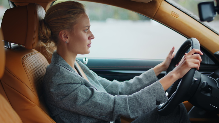 Side view disappointed business woman punching steering wheel at car. Angry businesswoman sitting at luxury car. Confused executive woman standing in traffic jam at car.