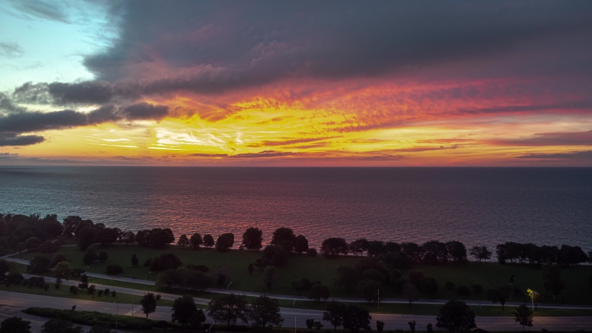 Chicago, IL - July 17th, 2017: The sky erupts with pink, orange and yellow colors as traffic begins to pick up along Lake Shore Drive in the Edgewater neighborhood early in the morning.