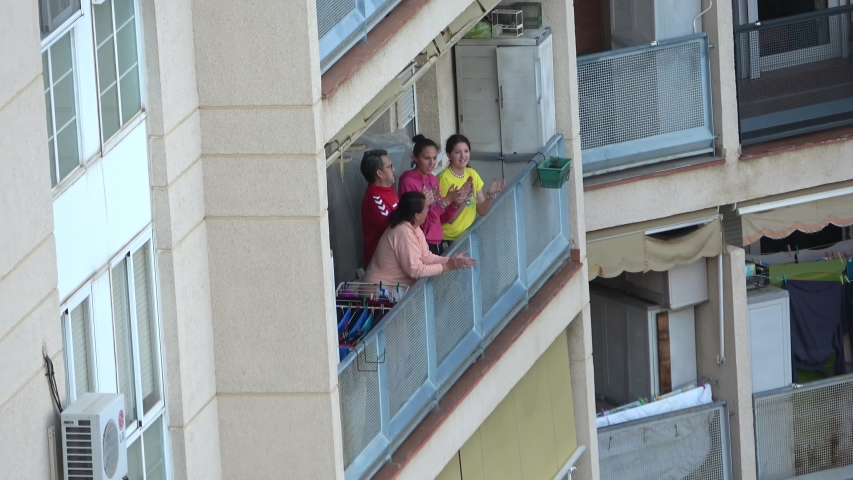 Huelva, Spain - April 8, 2020: Citizens staying at home and clapping everyday on balconies at 8 PM during the epidemic period of deadly coronavirus. People in quarantine in Spain