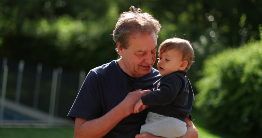 Grand-father holding baby infant in arms outside in backyard. Grand parent bonding with grand-child