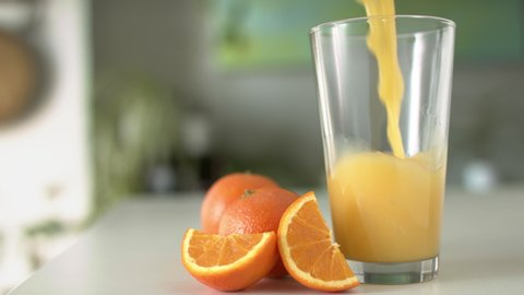 Healthy orange juice in a glass and oranges. Juice splash slow motion footage.  Closeup footage in 4K shot on RED.