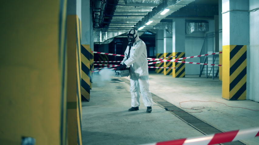 Coronavirus, Disinfection concept. Disinfector is fumigating empty premises with chemicals Royalty-Free Stock Footage #1050175525