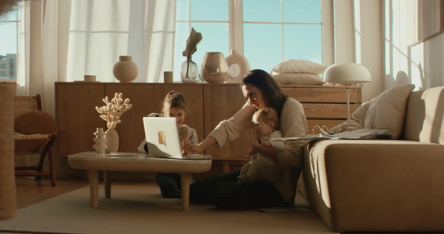 Mother working from home, having a phone call, while her daughters distract her and drawing attention. Shot on RED Dragon | Shutterstock HD Video #1050188092