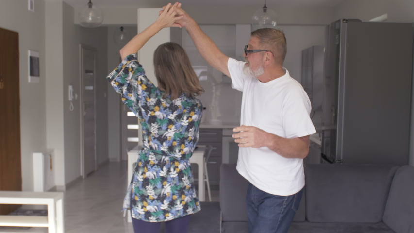 Happy senior couple dancing laughing in the kitchen. Beautiful romantic middle aged older grandparents relaxing having fun together at home celebrating anniversary enjoy care love tenderness #1050198166