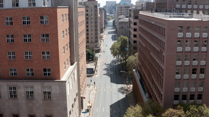 An aerial view of an empty street lined by tall buildings in Johannesburg city centre, during the covid-19 coronavirus lockdown.  | Shutterstock HD Video #1050198655